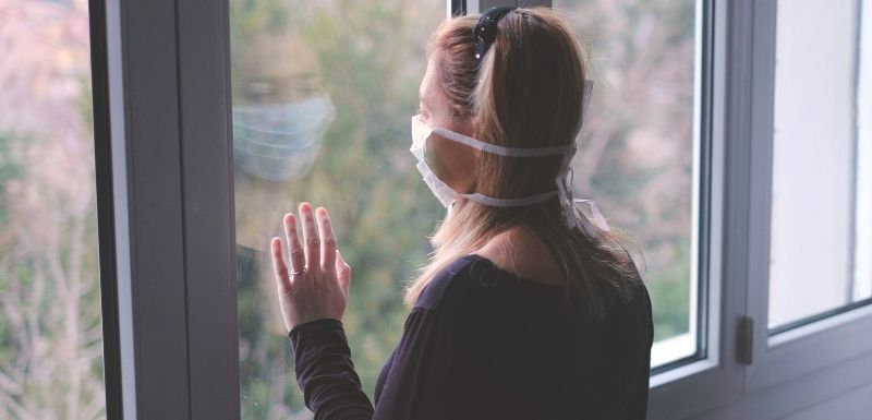 Femme qui a peur de sortir de chez elle face à l'épidémie de covid-19