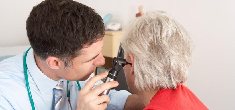 Médecin orl, qui regarde dans l'oreille d'une patiente